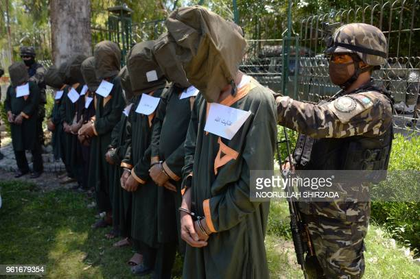 Taliban fighters stand handcuffed as they are presented to media in Jalalabad on May 23 2018 Afghan security forces have detained 13 alleged Taliban...