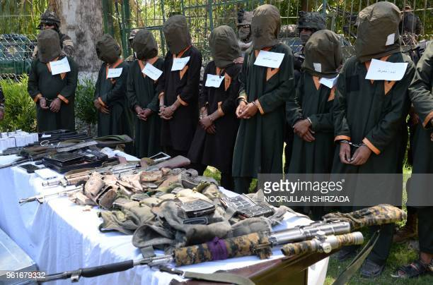 Taliban fighters stand handcuffed near seized weapons as they are presented to media in Jalalabad on May 22 2018 Afghan security forces have detained...
