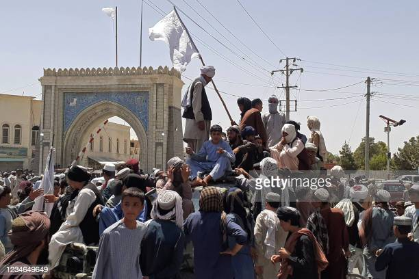 Taliban fighters stand on a vehicle along the roadside in Kandahar on August 13, 2021.