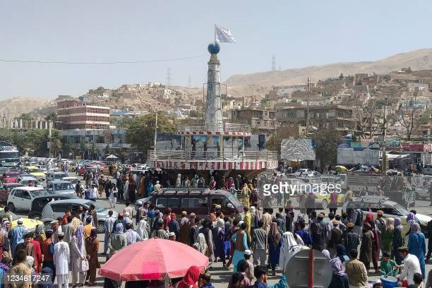 Taliban flag is seen on a plinth with people gathered around the main city square at Pul-e-Khumri on August 11, 2021 after Taliban captured...