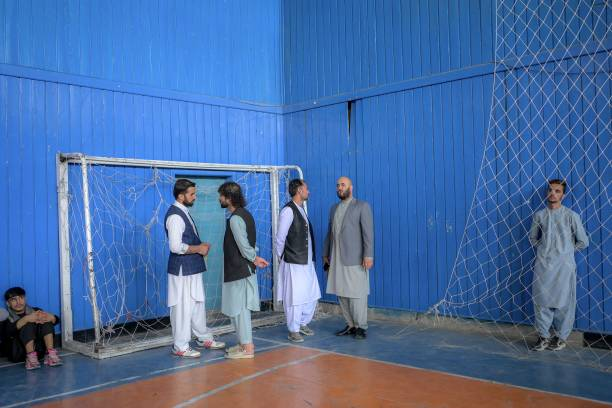 Taliban members chat as youths show their skills during an event organised for the visit of Taliban's director of physical education and sports...