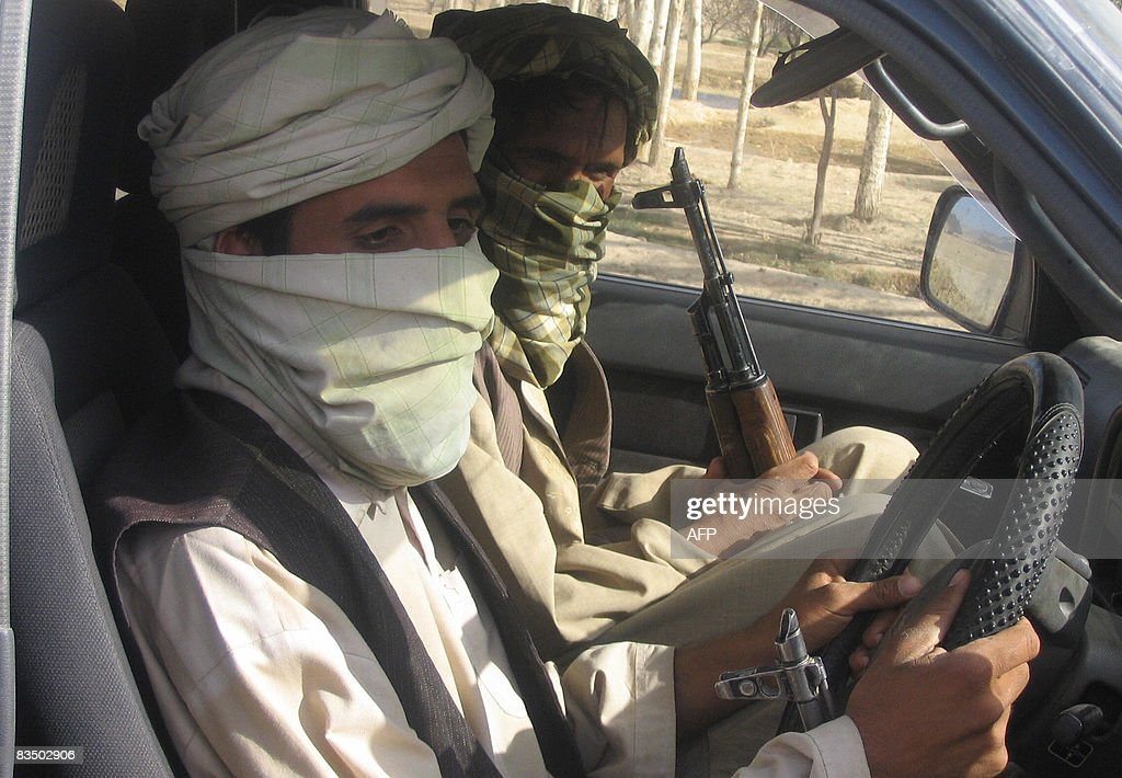 KHORAM Taliban militants pose with their weapons as they drive their car in Maydan Shahr in Wardak province on September 25, 2008. We will behead him,' threatens a 25-year-old, self-proclaimed Taliban, as day-long negotiations on the fate of a shopkeeper abducted five days ago reach a critical point. Four worried-looking male relatives of captured Abdul Ahmad sit with their backs against the wall in a house of a low-level Taliban commander in a part of Wardak province where the militants are in control, not the government. AFP PHOTO /Sharif KHORAM