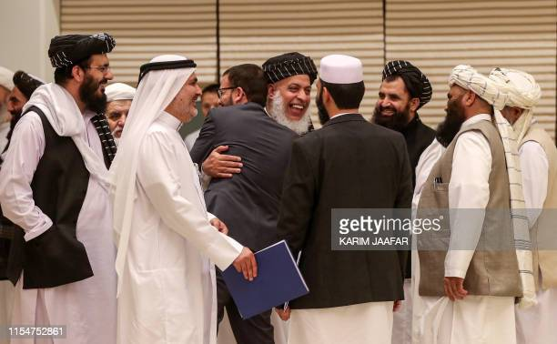 Taliban negotiator Abbas Stanikzai embraces a man as he attends with other Taliban members, including former US-held Guantanamo detainee Mohammad...