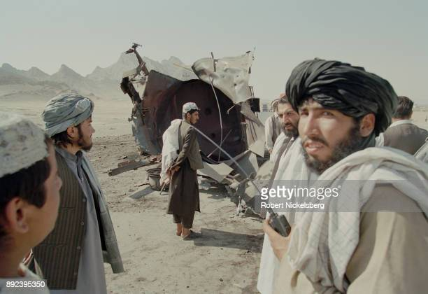 Taliban officials look at a destroyed fuel truck following a massive bombing operation by US and NATO planes October 31 2001 in Kandahar Afghanistan...