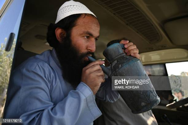 Taliban prisoner drinks water from a canister as he sits on a vehicle during his release from the Bagram prison, next to the US military base in...