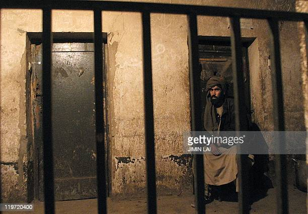 A Taliban prisoner sits outside his cell in a prison in the Afghan capital Kabul late 22 January 2002 Three hundred taliban fighters captured in the...