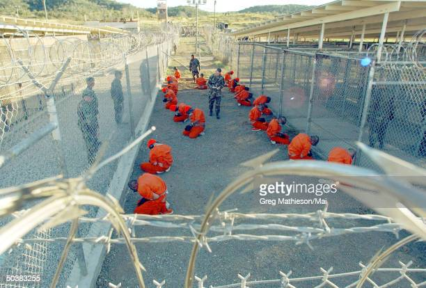 Taliban prisoners in orange jumpsuits sitingt in holding area under the watchful eyes of military police at Camp X-Ray at Naval Base Guantanamo Bay,...