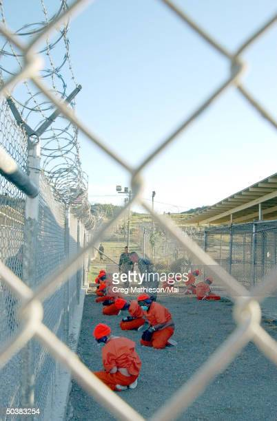 Taliban prisoners in orange jumpsuits sitting in holding area under the watchful eyes of military police at Camp XRay at Naval Base Guantanamo Bay...