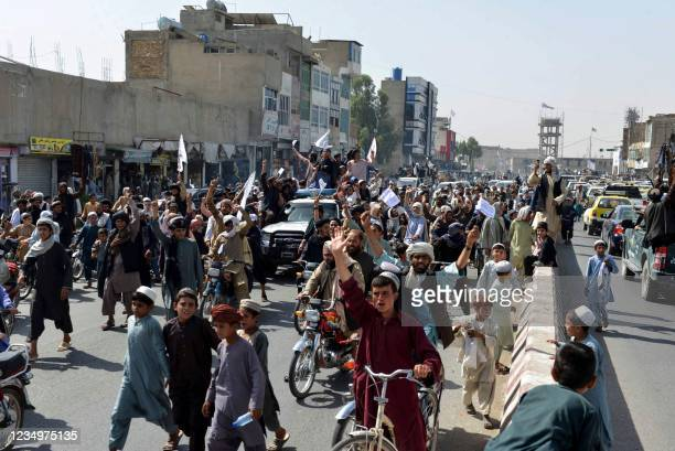 Taliban supporters shout slogans and wave Taliban flags as they march along a street in Kandahar on August 31 as they celebrate after the US has...