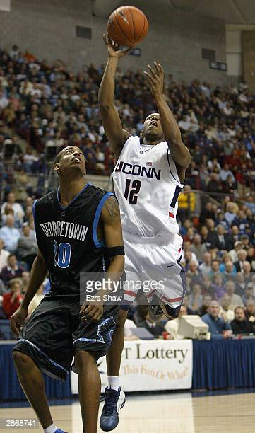 Taliek Brown of the UCONN Huskies shoots over Darrel Owens of the Georgetown Hoyas January 14, 2004 at the Gampel Pavilion in Storrs, Connecticut....