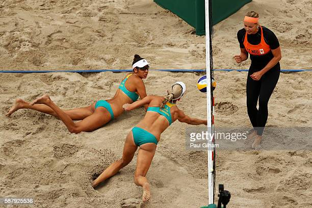Taliqua Clancy and Louise Bawden of Australia dive for the ball against Madelein Meppelink of the Netherlands during their women's prelimiary pool F...
