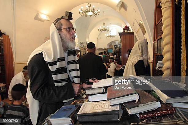 A Talith over his shoulders and a set of Tefillin on his head and arm a man prays at a synagogue in the tomb of secondcentury Jewish sage Rabbi...