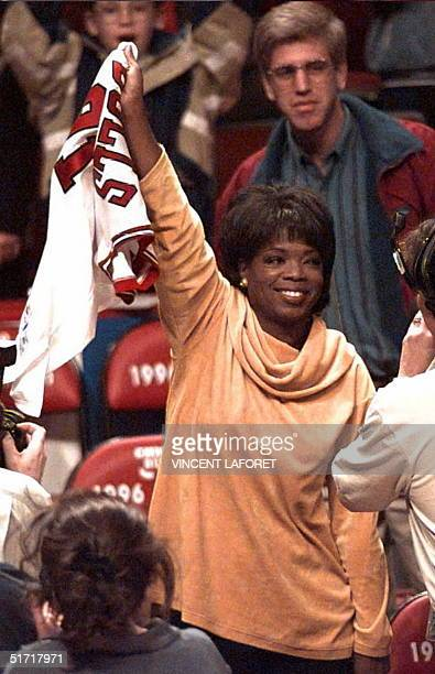 US talk show host and actress Oprah Winfrey waves Chicago Bulls forward Dennis Rodman's jersey after Rodman tossed her the jersey 07 May 1996 at the...