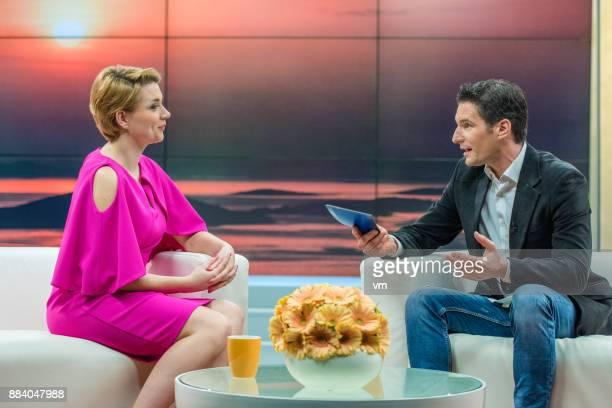 Talk show host interviewing a woman