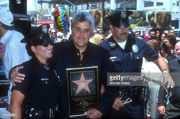 Talk show host Jay Leno stands between two policemen at a ceremony honoring Leno onto the Hollywood Walk of Fame April 27 2000 in Hollywood Leno...