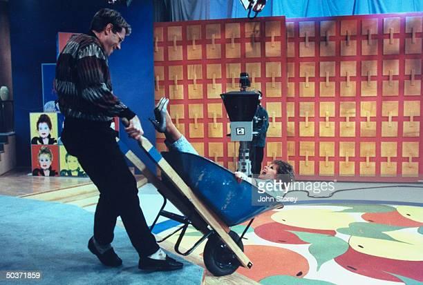 TV talk show host Jim J Bullock wheeling cohost Tammy Faye Bakker Messner in wheelbarrow on the set of their show The Jim J Tammy Faye Show