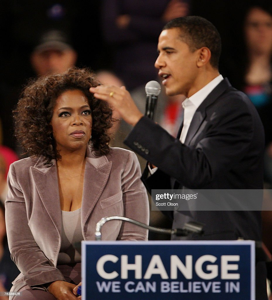 Talk show host Oprah Winfrey (L) listens as Democratic presidential hopeful Sen. Barack Obama (D-IL) addresses a crowd gathered for a campaign rally December 8, 2007 in Des Moines, Iowa. Obama and Winfrey are scheduled to make two stops in Iowa before heading off to campaign events in South Carolina and New Hampshire tomorrow.