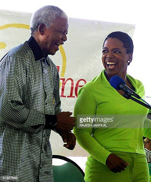 Talk show host Oprah Winfrey smiles at former South African President Nelson Mandela as he performs the Madiba jive dance 11 December 2002 at a...