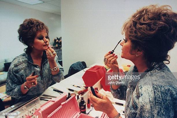 TV talk show host Tammy Faye Bakker Messner applying mascara to eyelashes in mirror in dressing room