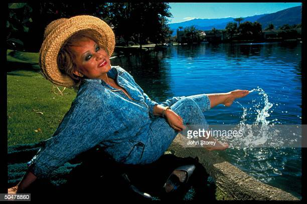 TV talk show host Tammy Faye Messner dipping bare feet in lake nr her home