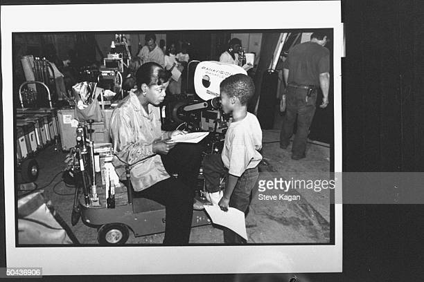 TV talk show host/actress Oprah Winfrey holding script as she chats w child actor Norman Golden II while sitting on motorized trolley equipped w...