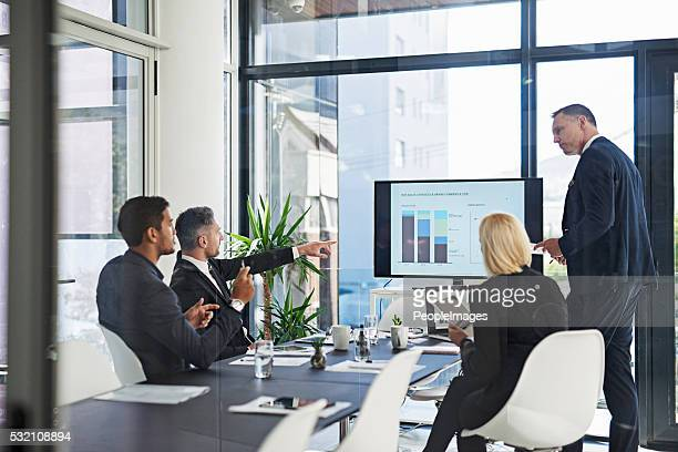 talking business in the boardroom - bedrijven financiën en industrie stockfoto's en -beelden