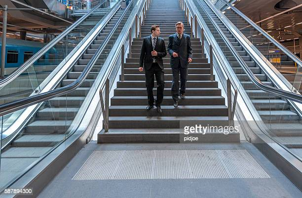 talking businessmen walking down the stairs in modern railroad station