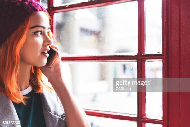 talking on a phone with friends in the privacy of a red phonebooth - telephone box stock pictures, royalty-free photos & images