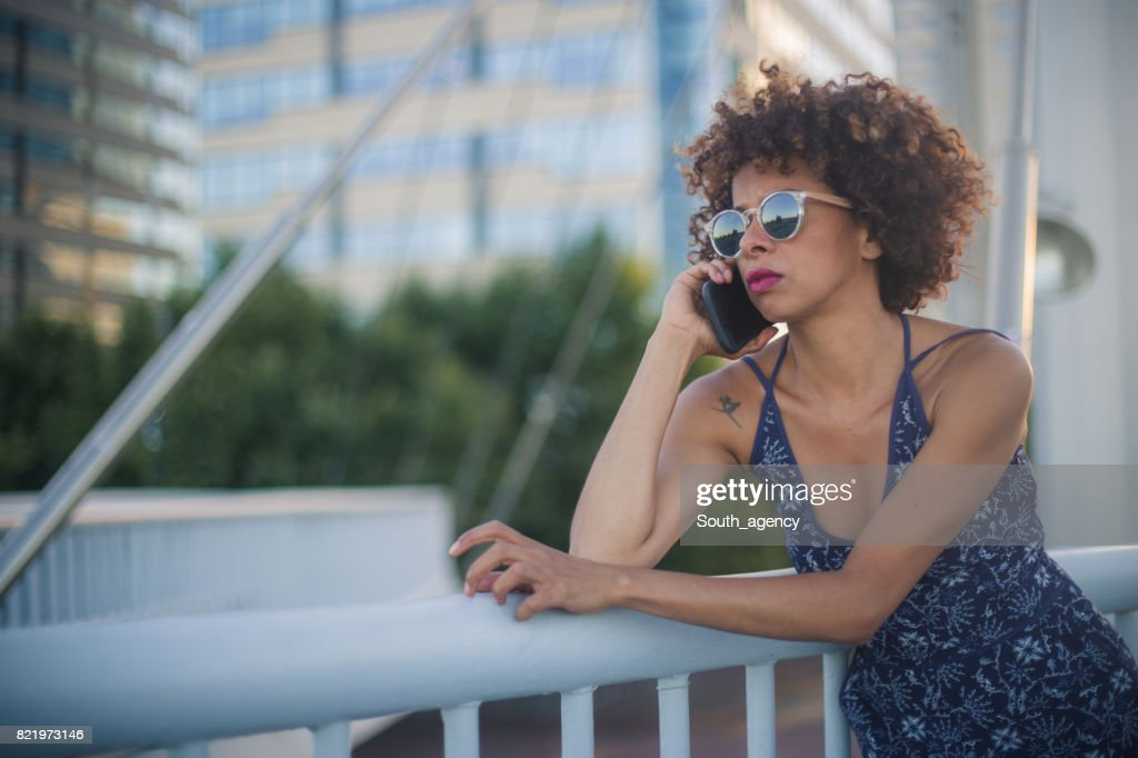 Talking on mobile phone outdoors : Stock Photo