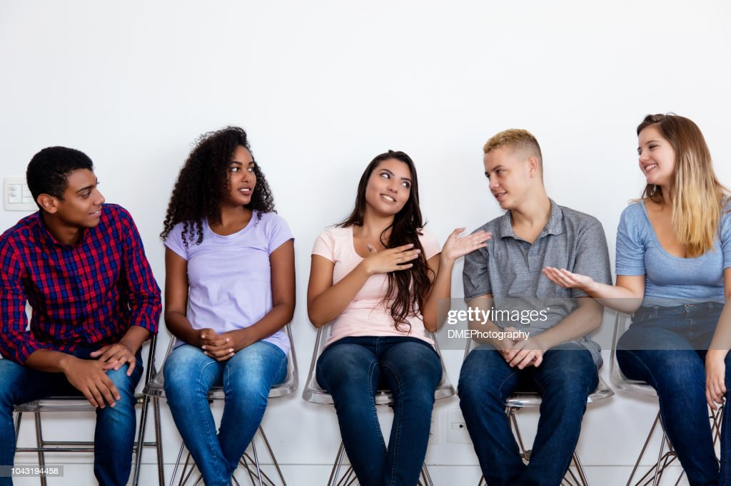 Talking young adult group of people in waiting room : Stock Photo