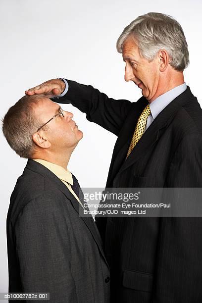 tall and short businessmen comparing height, profile - alto descripción física fotografías e imágenes de stock