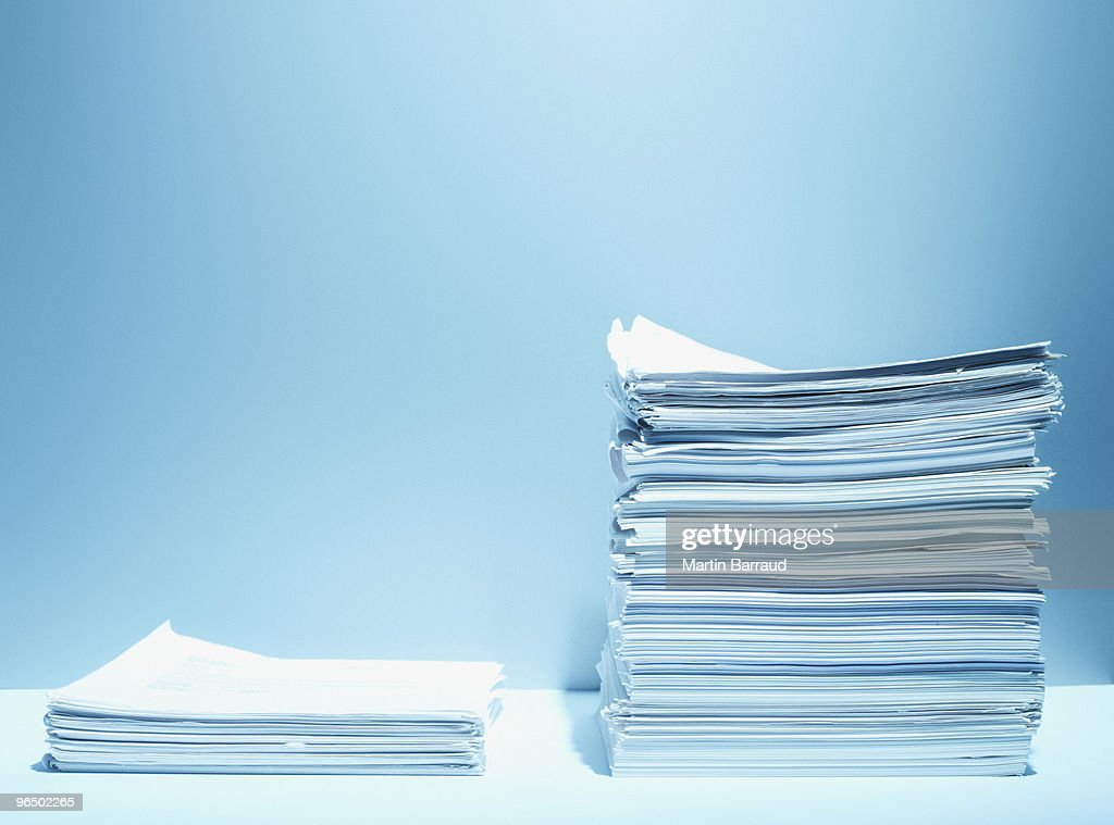 Tall and short stacks of paper : Stock Photo