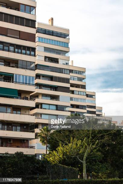 tall apartment complex with a bit of blue sky and white clouds to the right and some trees in the foreground - dorte fjalland fotografías e imágenes de stock