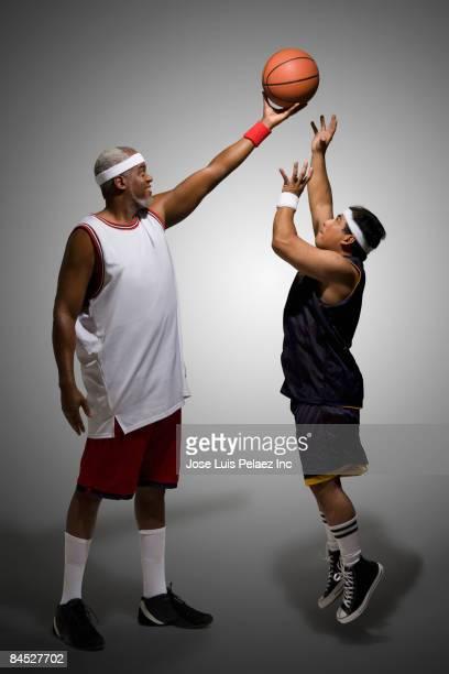 Tall basketball player keeping ball from shorter player