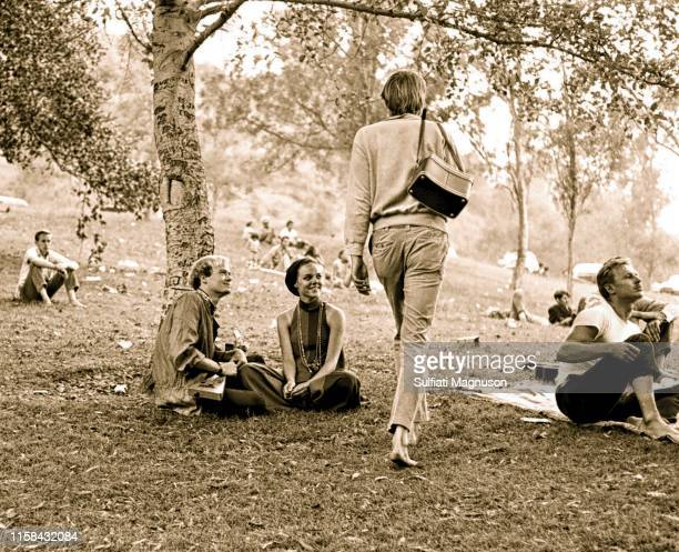 Tall, blond, barefooted man with a camera bag heading home, as a happy couple observe, several barefooted young men sitting on the grass at the 1st...