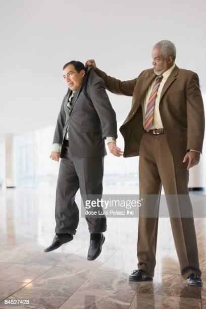 Tall businessman lifting short businessman
