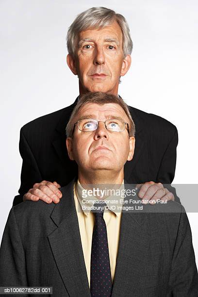 Tall businessman standing behind short colleague and looking at camera, front view