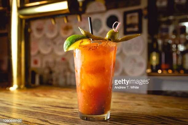 a tall cool back lit bloody mary drink sits on a wood bar counter - horizontal - bloody mary stock photos and pictures