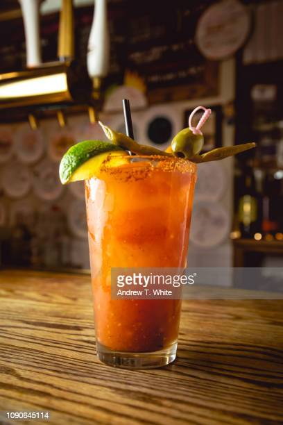 A Tall cool back lit Bloody Mary Drink Sits on a Wood Bar Counter - Vertical