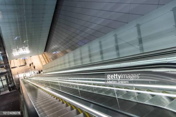 tall escalators descending to metroplatform at vijzelgracht - merten snijders stockfoto's en -beelden