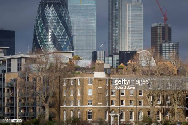 Tall financial properties in the City of London including the Swiss Re building left rise above modern riverside residential apartments and the...