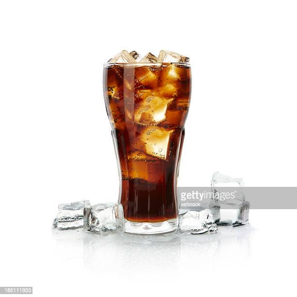 Tall glass of brown drink overflowing with ice cubes