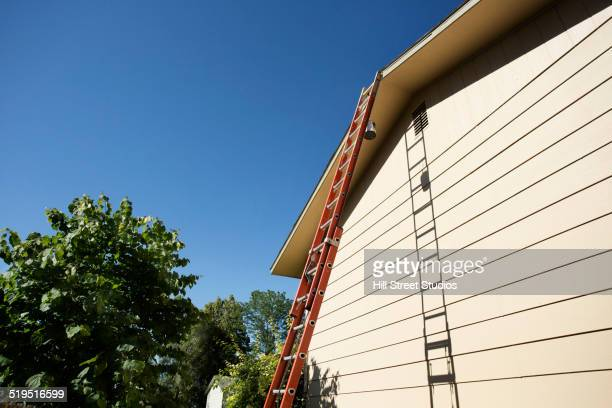 Tall ladder leaning on house