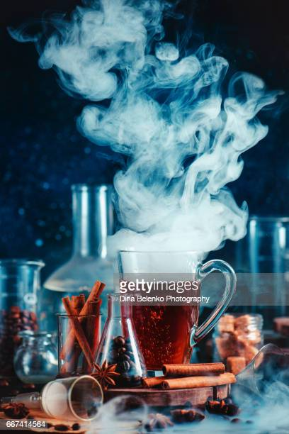 Tall latte glass with a cloud of steam, cinnamon and recearch items