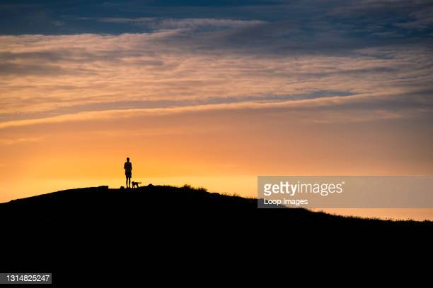 Tall man and his dog standing on the summit of Pentire Point East silhouetted by an intense sunset at Newquay in Cornwall.