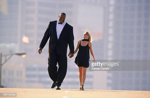 Tall man and short woman walking on street