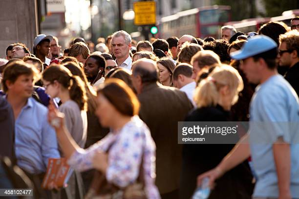 Tall man in a crowded intersection