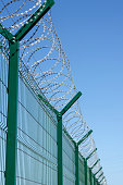 tall metal fence with barbed wire