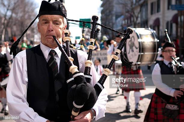 CONTENT] A tall middle aged Scottish piper in waistcoat and tie but no jacket looks downward as he plays the pipes in a parade The image was taken in...