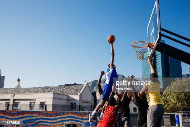 tall player floating in to score a basket - team sport stock pictures, royalty-free photos & images